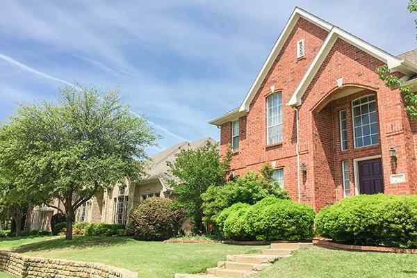 brick house with shrubs out front in katy texas