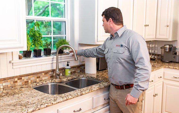 a pest control technician performing an interior inspection in a fairfax virginia home