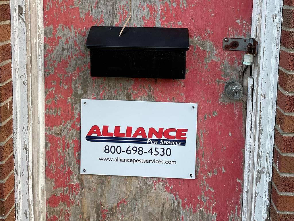 alliance pest services sign on door