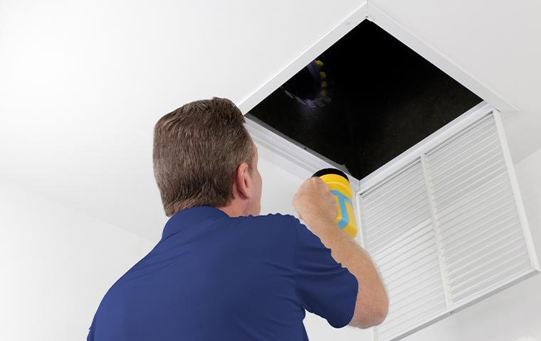 tech inspecting vent