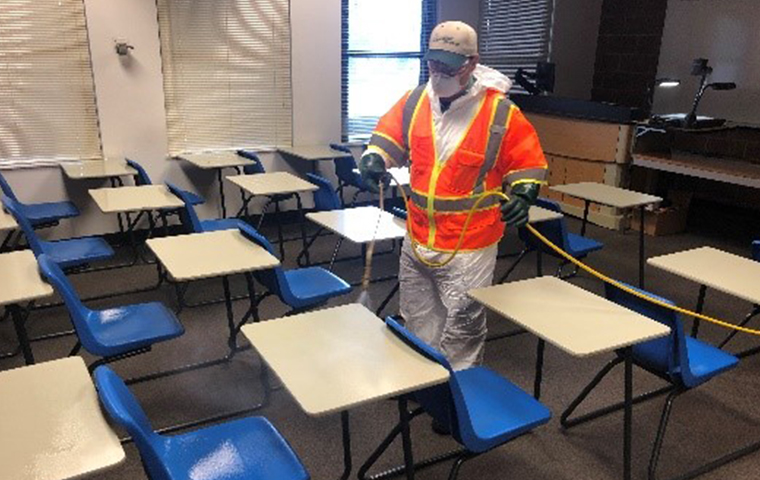 tech disinfecting a classroom