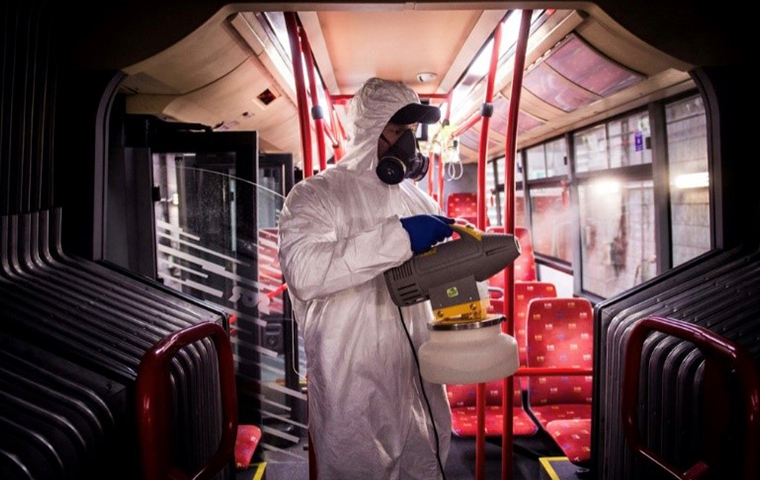 tech disinfecting a public bus