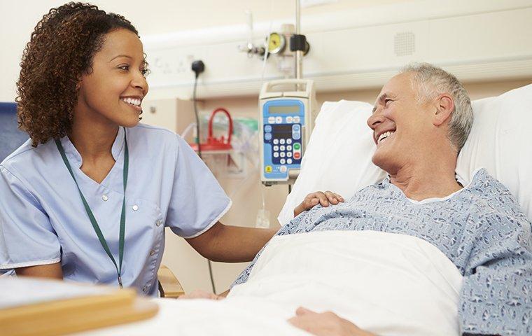 a female nurse talking with an elderly patient