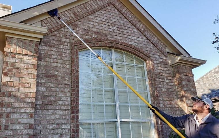 dancan technician cleaning a homes of spider webs