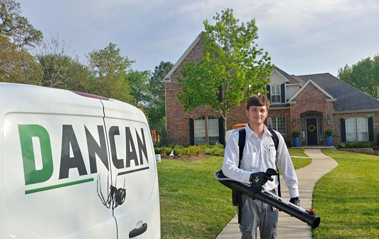 dancan technician standing near company vehicle parked in front of a house