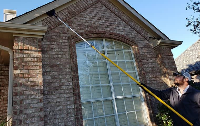 a dancan pest control service technician treating the exterior of a home in frisco texas