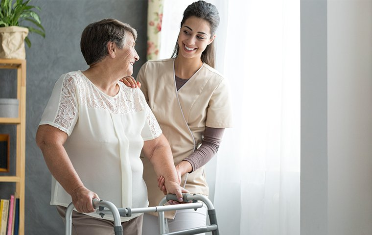a friendly nurse helping an elderly lady
