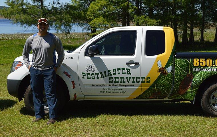 a pest control technician standing by his service truck