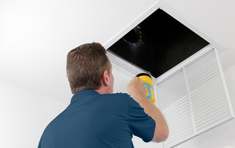 technician inspecting vent