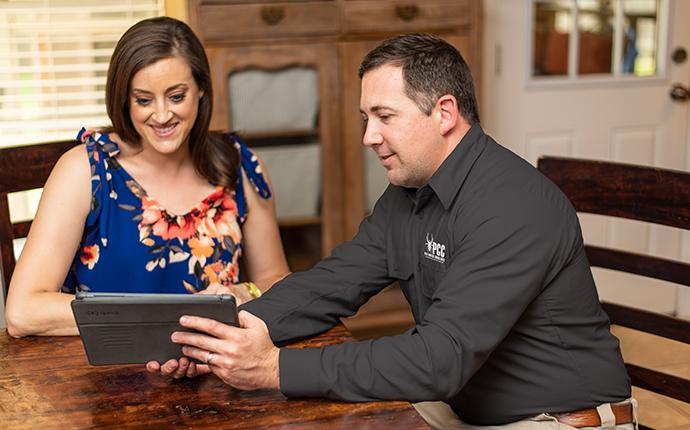 smiling woman meeting with her pest control consultants technician in dekalb illinois