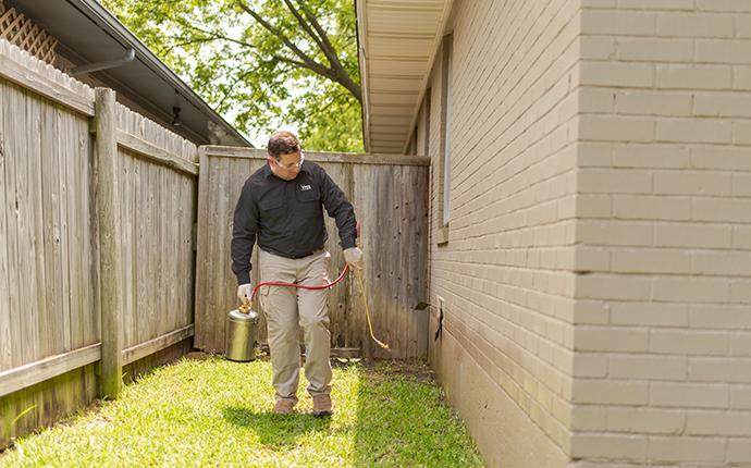 pest control consultants technician treating the perimeter of a dixon illinois home for pests
