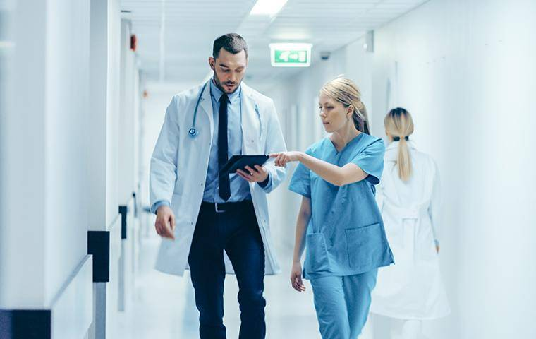 a doctor and nurse in a medical office hallway
