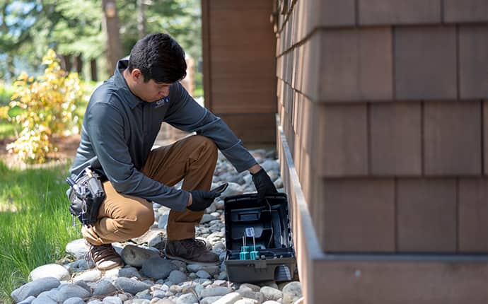 a prosite pest control service expert performing rodent control services outside of a home in washington