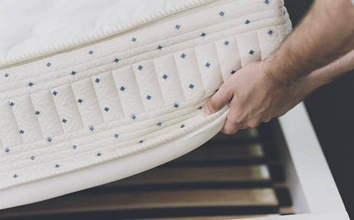 traveler inspecting hotel mattress for bed bugs