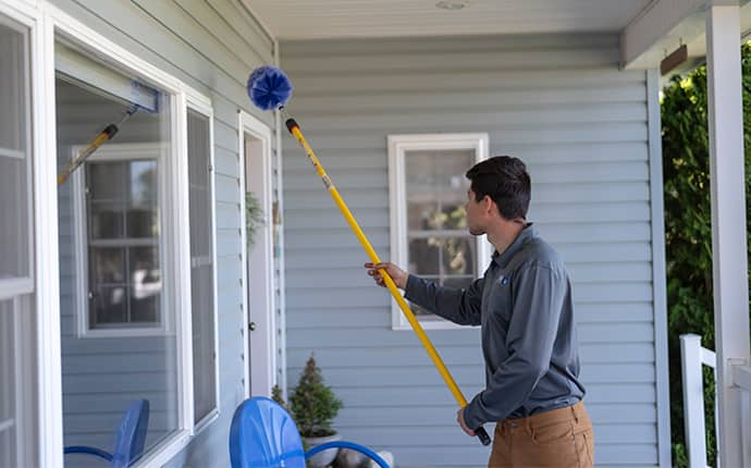 a prosite pest control service expert performing dewebbing services outside of a thorp home