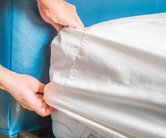 person looking in bed sheets for bed bugs