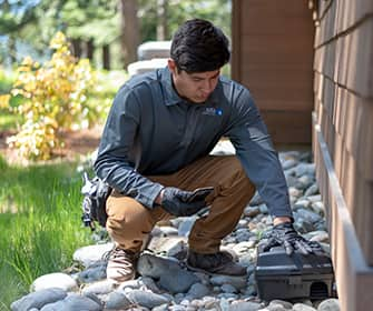 a prosite pest control service expert setting up a rodent station outside of a home in washington