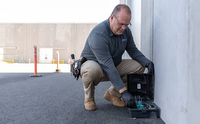 a prosite pest control service expert setting up a rodent control station outside of a commercial business in central washington