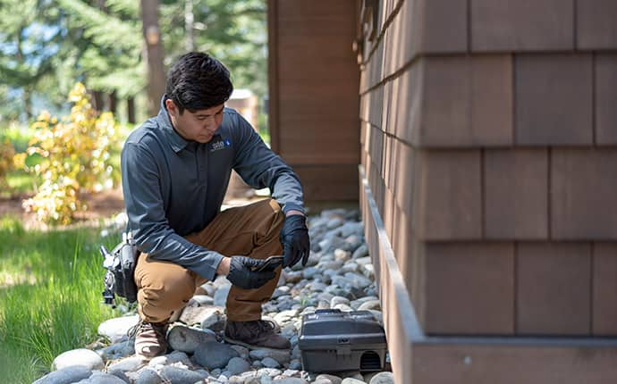 a prosite pest control service expert setting up a rodent control station outside of a home in central washington
