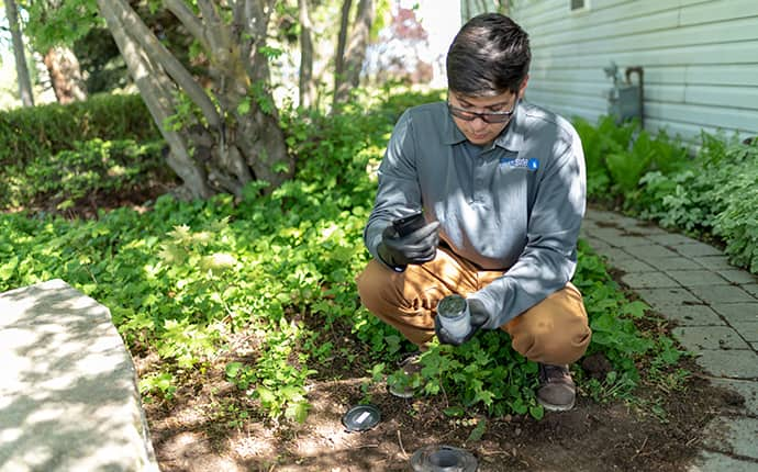 a prosite pest control service expert installing a termite station outside of a home in central washington