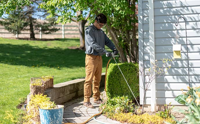 a prosite pest control service expert digging a trench around a central washington home