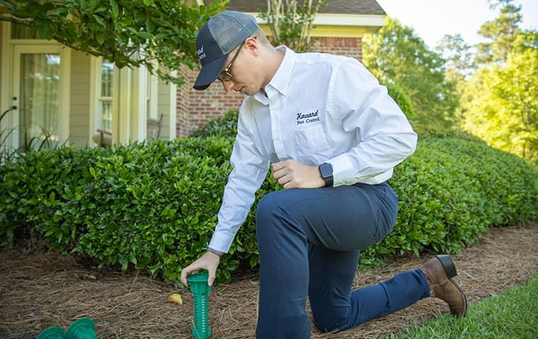 a technician inspecting a termite bait station in the yard of a home in new orleans