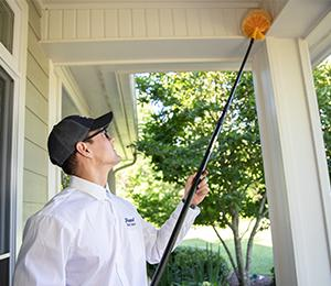 havard technician sweeping the eaves of a mississippi home
