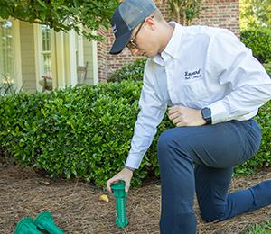 a havard technician checking a termite bait stations outside of a mississippi home