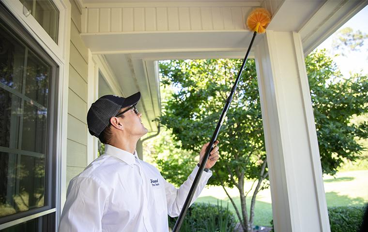 havard pest control technician removing pests on porch
