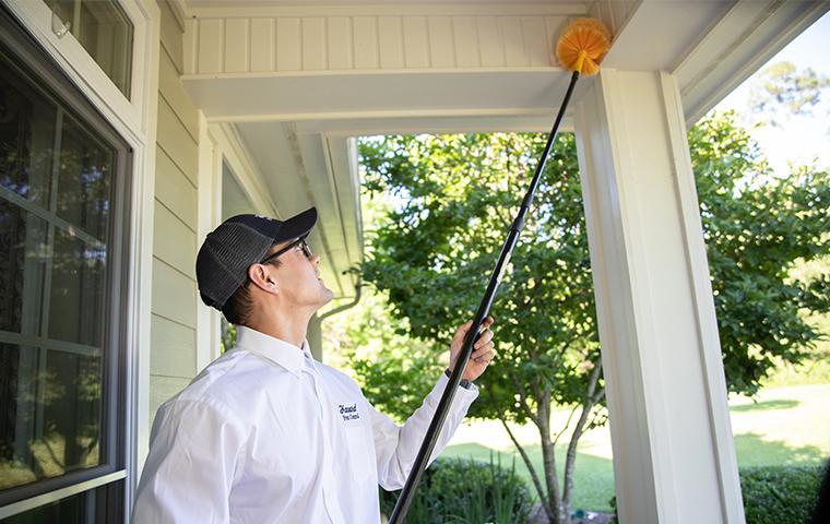 havard pest control technician removing pests on porch