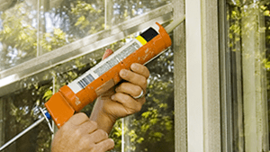 technician applying caulk to window