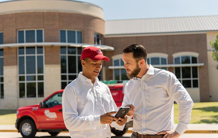 pest control technician and business owner discussing inspection report