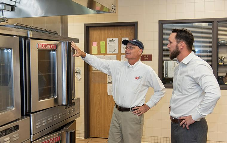 business manager with adams tech inspecting for pests