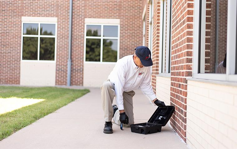 tech checking rodent station outside commercial building