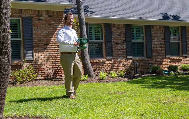 tech using granular spreader outside home in dallas texas