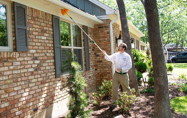 adams tech using a dewebber pole on exterior of house