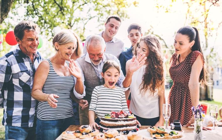 family celebrating outdoor birthday party