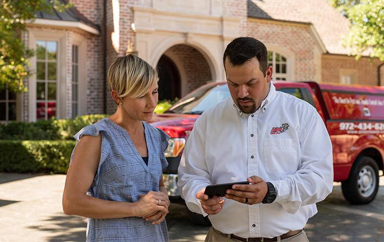 homeowner and tech looking at a cellphone in the techs hand