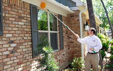 pest control tech performing exterior dewebbing treatment