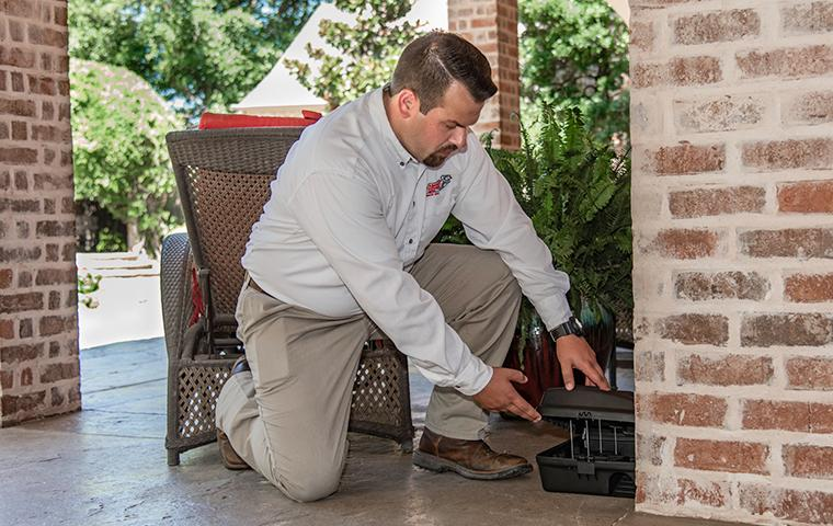 adams tech checking a rodent station outside a home in plano texas