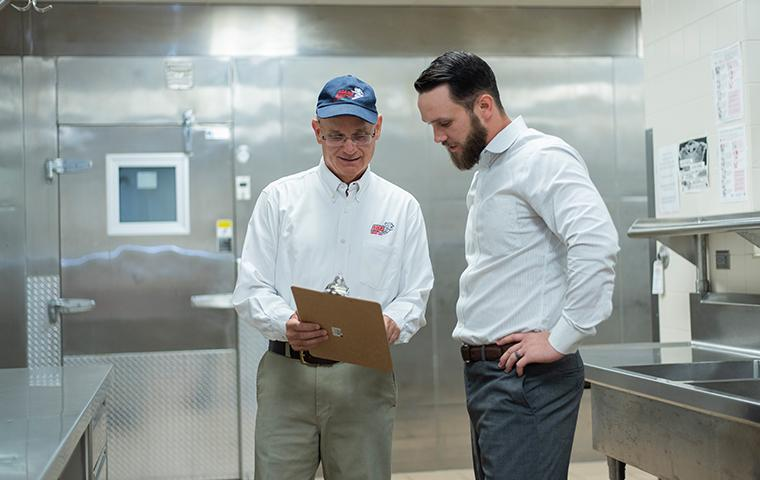 pest control technician discussing service plans with business owner