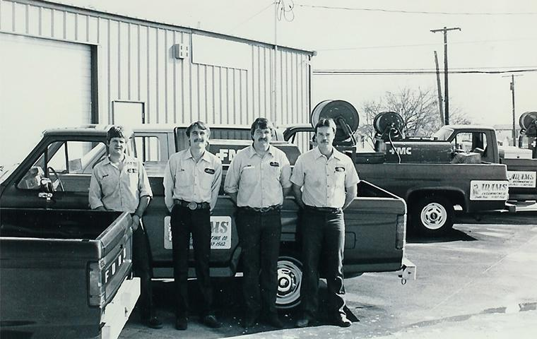 old picture of adams team in front of truck