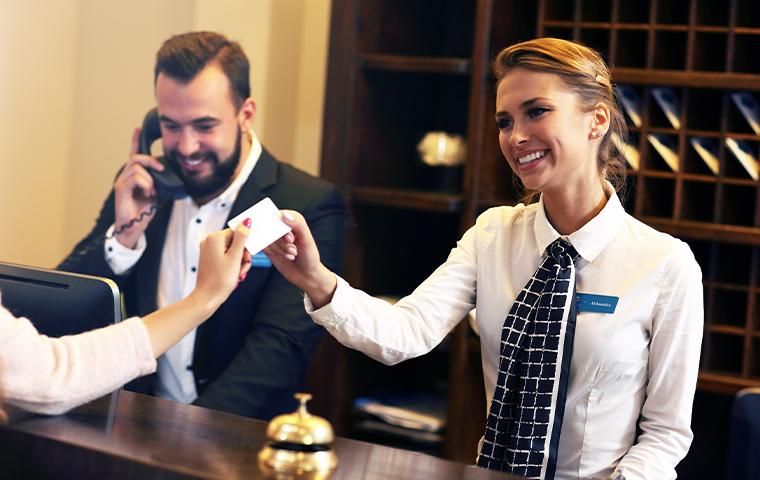 hotel front desk woman handing key card to off screen client