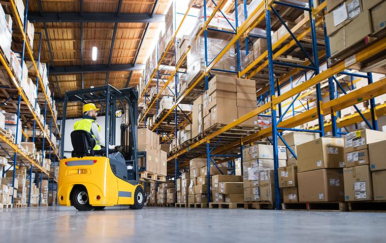 forklift maneuvering boxes in a warehouse setting