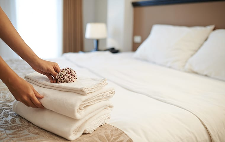 a hospitality worker folding towels inside of a hotel room serviced by thermalrid in nashvillle tennessee