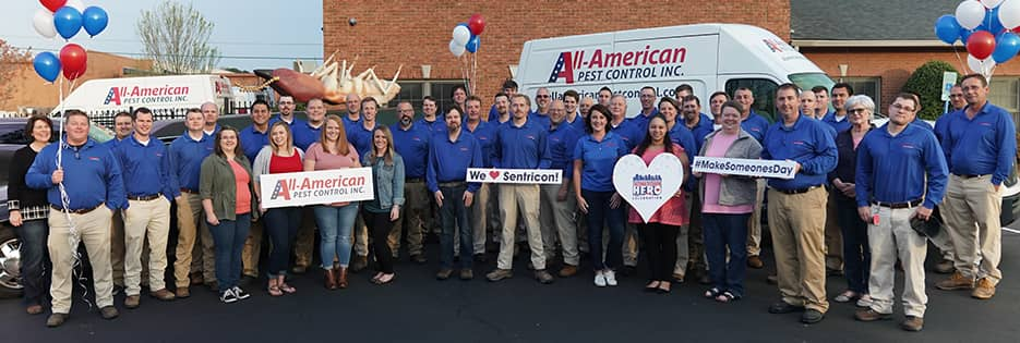 the all-american pest control team standing in front of a company van with signs to celebrate the second annual hometown hero award
