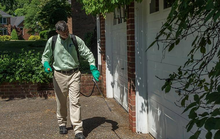 nashville tn pest control tech treating exterior of home