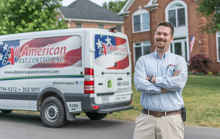 all american tech standing in front of service vehicle outside of clients home in spring hill tennessee