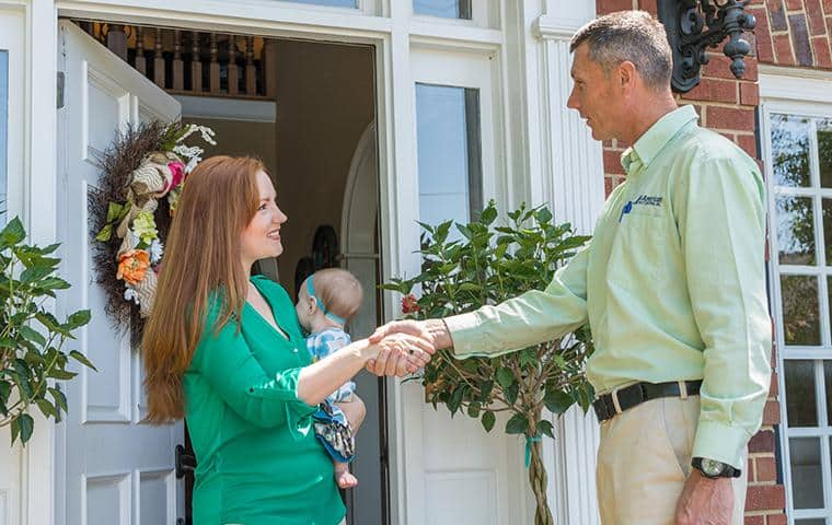 pest control technician greeting nashville homeowner
