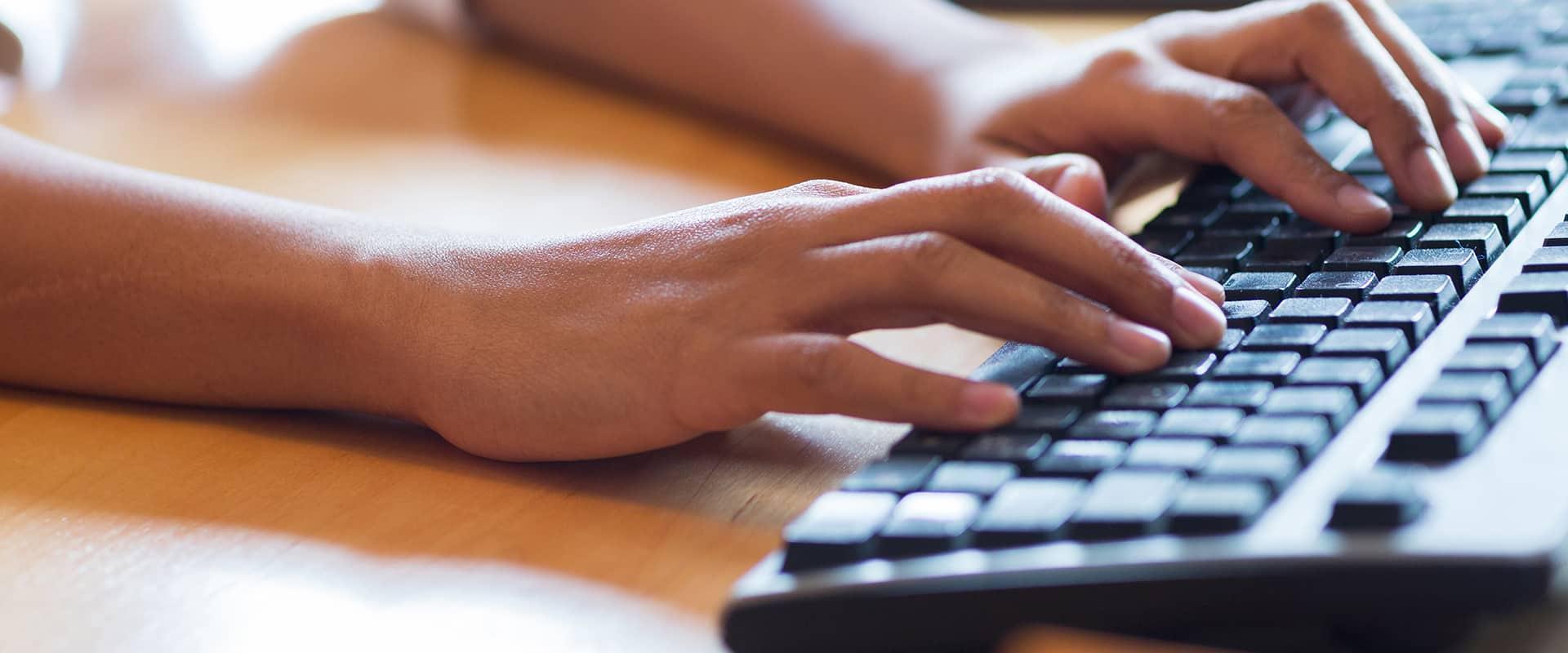 a person typing on a keyboard in kill devil hills north carolina